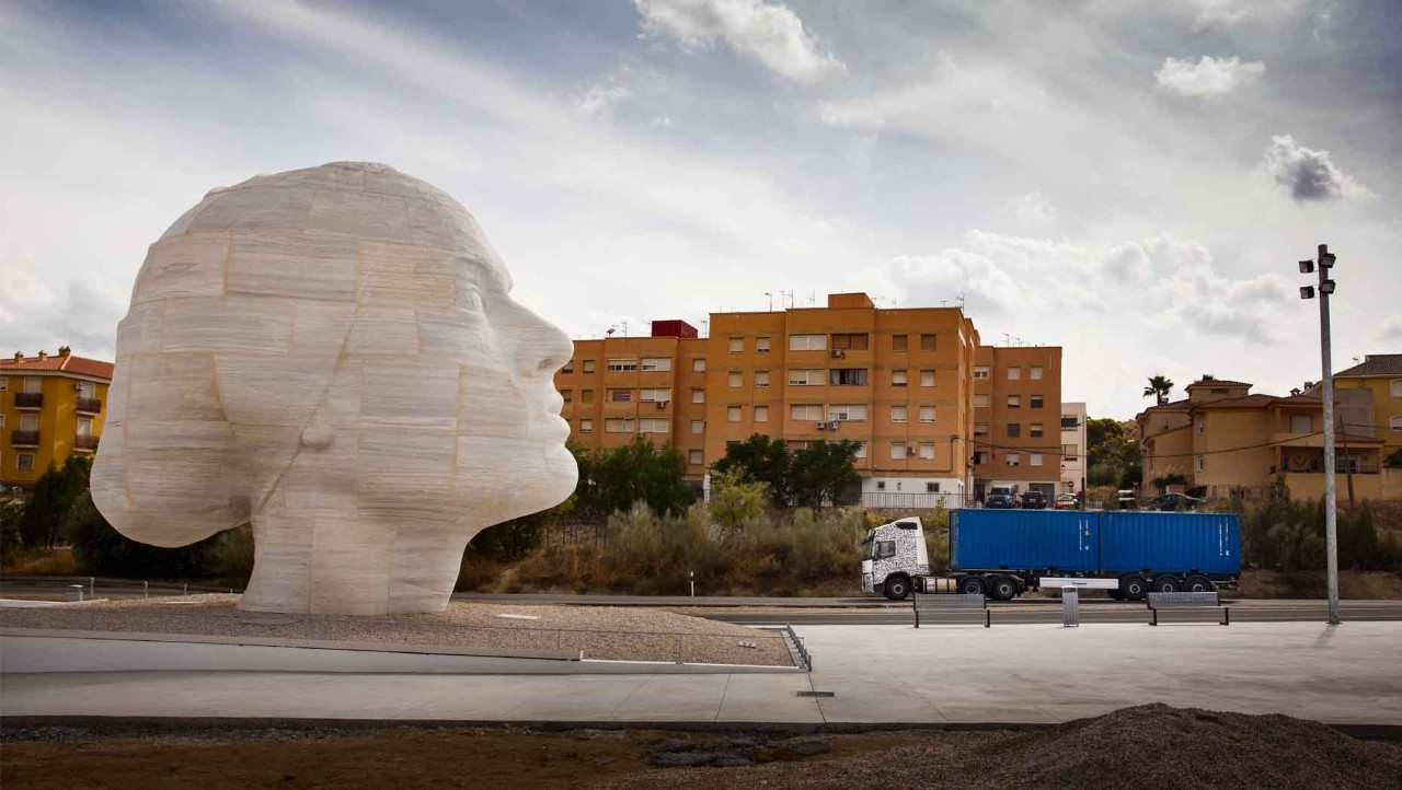 A test truck passes a marble statue in Spain