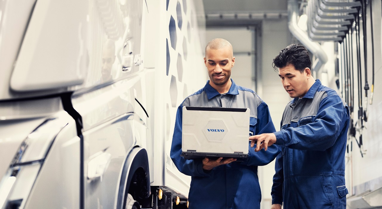 To serviceteknikere fra Volvo ser på en bærbar PC mens de står ved siden av en lastebil